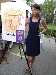Lady with her shop's placard.